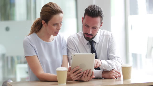 Colleagues using a digital tablet in a meeting