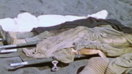 A collection of corpses laying side by side and covered with bloody limbs hanging out from the covering / Iwo Jima Japan