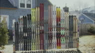 WS Collection of skis leaning against fence / Rutland, Vermont, USA