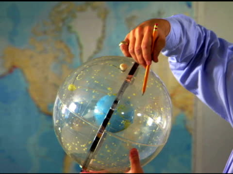 College professor lecturing and holding globe