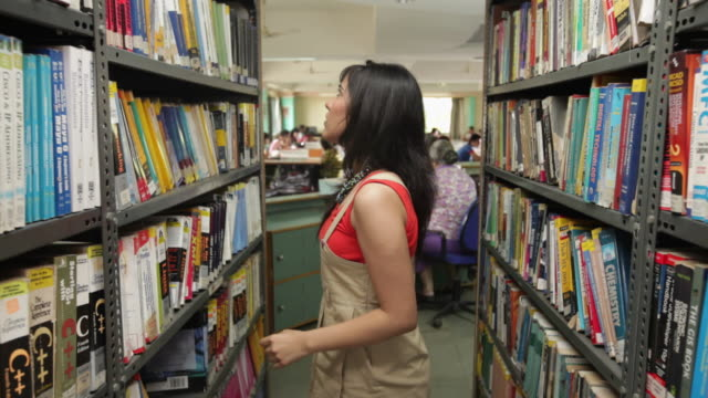 College student searching book in library