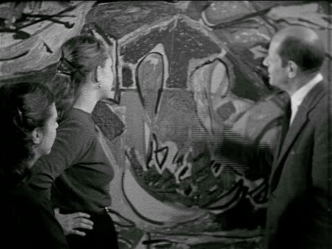 College students standing w/ American painter Jackson Pollock standing gesturing talking in front of his abstract expressionist painting displayed at...