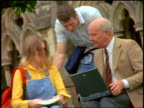 2 college students talking with senior male professor sitting + using laptop outdoors / England