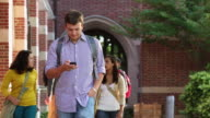 MS TS College Students Walking on Campus, Texting on Cell Phone / Richmond, Virginia, USA