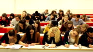 College Students writing in University Lecture hall
