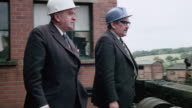 MONTAGE Colliery yard, administrators with hard hats walking and pointing down at yard, tracks running through yard, water pouring out of aqueducts, worker checking pipes / Wales, United Kingdom