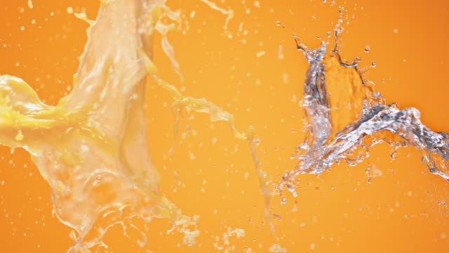 SLO MO Collision of juice and water on orange background