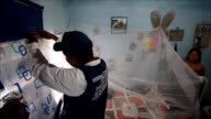 Colombian health officials do awareness campaigns and plant guppy fish in water drainage system and distribute mosquitos nets to pregnant women in a...