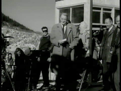 Colorado governor W Lee Knous standing on ski lift w/ Walter Paepke BG first person riding in ski lift townspeople cheering General Jacob Dever...