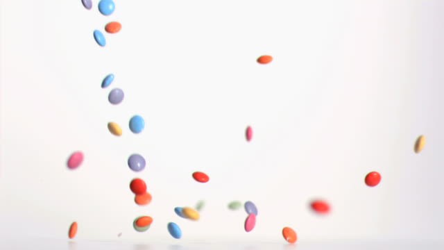 Colored candies falling in super slow motion