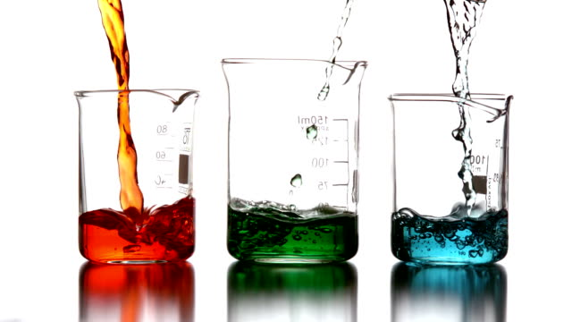 Colored chemicals pouring into beakers