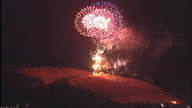 Colorful fireworks light up the night sky above a mountain / Traditional annual festival in Nara Japan / Shot on January 28 2012