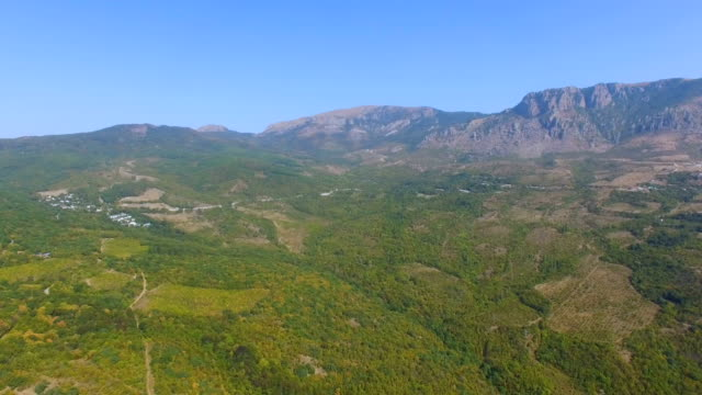 AERIAL: Colorful forests at foot of beautiful mountainss
