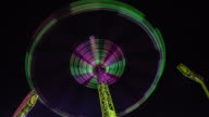 Colorful fun fair attraction at night - Time Lapse
