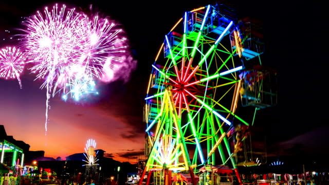 colorful light ferris wheel with fireworks