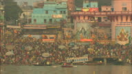 Colorful murals of Hindu gods overlook hundreds waiting to bathe in the Ganges.