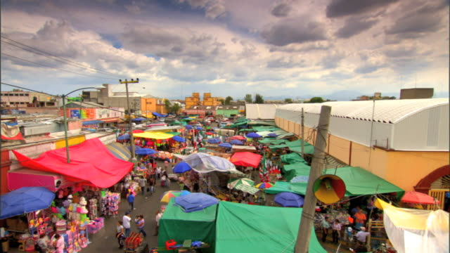 Colorful street market tents stretching into BG w/ unidentifiable people walking through buildings distant BG cloudy sky BG