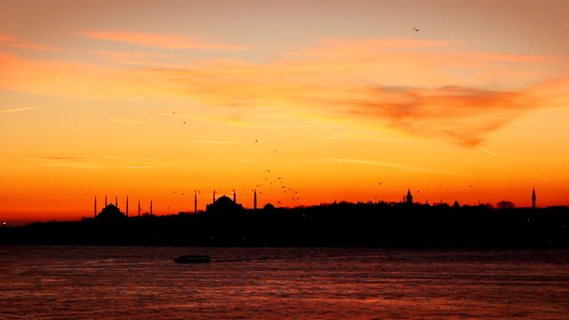 Colorful Sunset of Flocks  Birds flying over the silhouettes Mosques