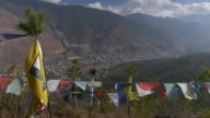 Colourful prayer flags are tied on lines in front of the city of Thimphu