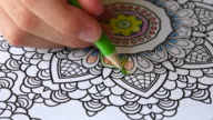 Colouring book for adults: hand of person using colour pencil to draw inside the 'mandala'