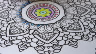 Colouring book for adults: time lapse hand of person using colour pencil to draw inside the 'mandala'