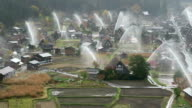 Columns of water reaching up to 30 meters high are discharged over traditional gasshozukuri farmhouses during an annual waterdischarge drill in the...