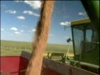 Combine harvester hopper pours wheat into truck loaded truck drives away