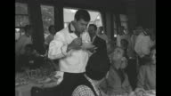 MS comedian Jerry Lewis dressed as a waiter takes customer's soup bowl off table in restaurant eats from it / WS Lewis carries tray laden with dishes...