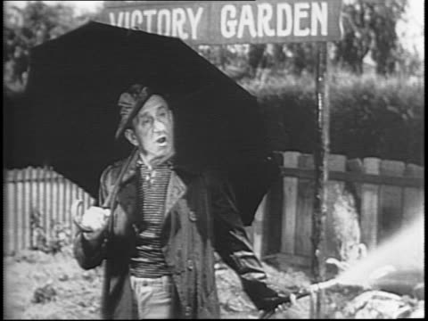 A comedic bit about wartime rationing with Victory Gardens / Two neighbors stand in their gardens outside / one has on a raincoat and umbrella as he...