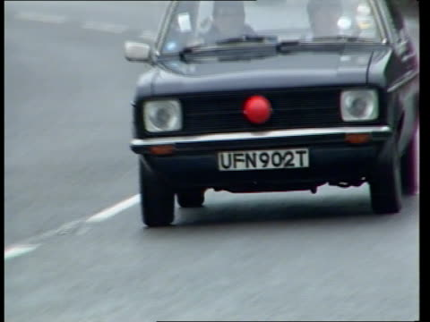 Comic relief day 1989 MS Ford Escort with red nose on grille along around bend PAN Wells St Ford Escort with red noses all over bonnet along PAN RL...