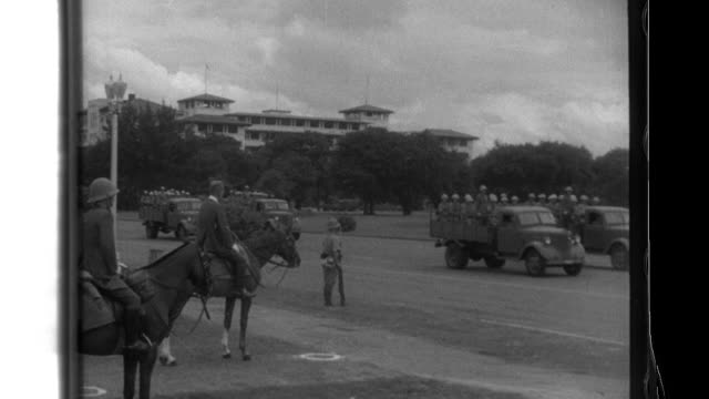 Commander Honma on horseback reviews Imperial Japanese Army motorized and infantry troops who parade through Luneta Park and then past crowds on city...