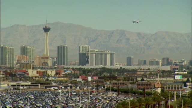 Commercial aircraft ascending on southern approach to McCarran International Airport runway jet passing Stratosphere hotels casinos along Las Vegas...