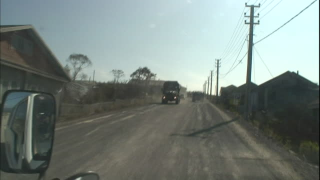 Commercial and passenger vehicles move on a gravel road as they pass residential buildings in Kunashiri Island.