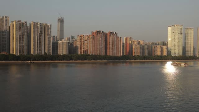 Commercial and residential buildings stand along the Pearl River in Guangzhou China on Monday Oct 30 A boat sails along the Pearl River as...