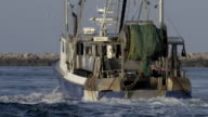 Commercial fishing boat heading out to sea from a small New England fishing village - view from rear as boat goes away