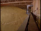 Reform LIB ENGLAND Lincolnshire Mountain of grain piled up in warehouse PAN Cotswolds EXT Tractor pulling equipment along thru field PULL OUT towards...