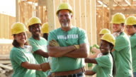 community leader with diverse group of volunteer teenagers on a construction site