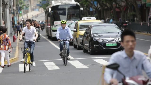 A commuter riding an Ofo Inc bicycle waits with other commuters at a traffic light in Shanghai China on Thursday May 25 A commuter riding an Ofo Inc...