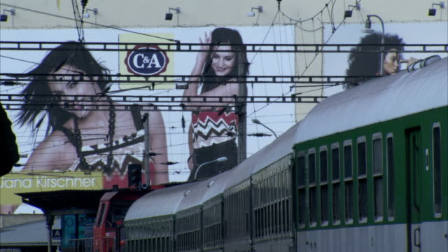 A commuter train passes by a billboard. Available in HD