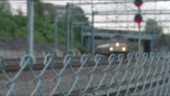 Commuter train slowly passing the camera.  Shot begins with out-of-focus chainlink fence with train approaching and then camera focuses on train as it passes.
