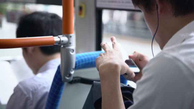 MS Commuter using smartphone on bus