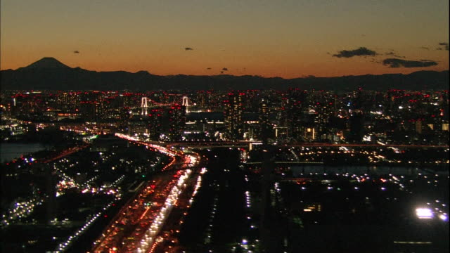 Commuter vehicles use their headlights as they travel on a busy Tokyo riverfront highway late in the day.