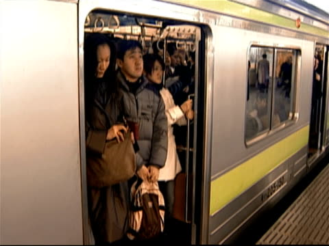 Commuters boarding crowded subway train stopped at Shinjuku Station platform at rush hour / doors on subway closing and train departing station / Tokyo, Japan