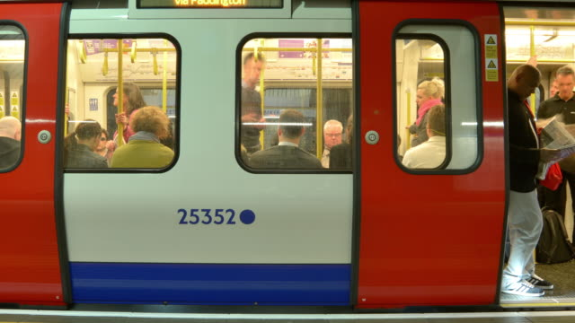 Commuters embarking on disembarking on the London Underground at Baker Street Station