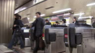 Commuters exiting through turnstiles in subway station / Tokyo