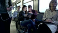 Commuters on a bus playing with digital tablet