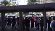 Commuters stand waiting for buses and Jeepneys at a bus stand in the Makati district of Manila the Philippines on Monday May 18 2015