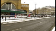 Commuters struggle to travel in London in heavy snow ENGLAND London People waiting in snow to cross main road / Pedestrians towards / Woman wearing...