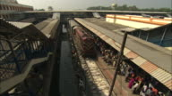 Commuters wait on a crowded train platform near filthy water in India.