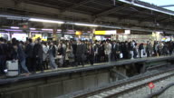 Commuters waiting at the JR Yamanote Line in Shinjuku for a train